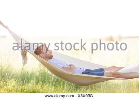 Jeune homme dormant dans un hamac d'été Banque D'Images
