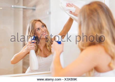 Jeune femme blonde miroir de nettoyage dans la salle de bains. Debica, Pologne Banque D'Images