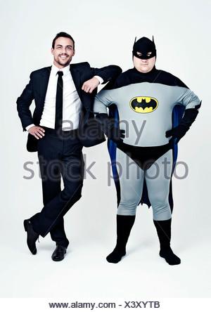 Athletic homme portant un costume à côté d'un gros homme habillé comme un super héros, Batman Banque D'Images