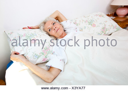 High angle view senior woman looking away while lying bed accueil Banque D'Images