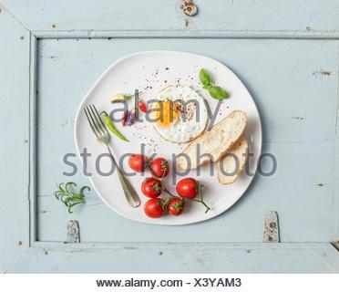 Le petit-déjeuner ensemble. Les tranches de pain frit, oeuf, tomates cerises, poivrons et les herbes sur une plaque en céramique blanc bleu clair au bac en bois Banque D'Images