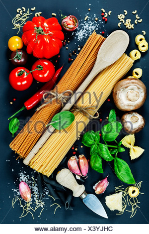 Ingrédients italien - pâtes, légumes, épices, fromage - sur fond sombre Banque D'Images