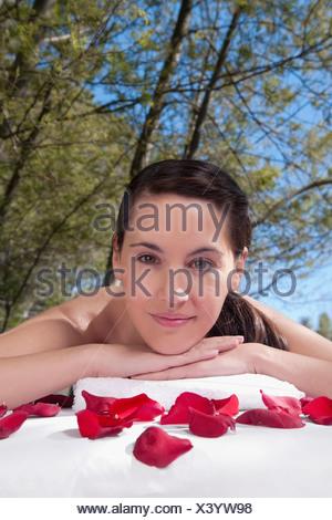 Portrait d'une femme allongée sur une table de massage avec des pétales de rose