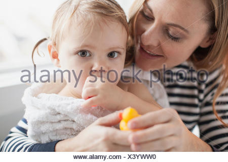 Mother holding baby girl wrapped in towel après bain Banque D'Images