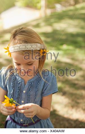 Fille jouant avec des fleurs en plein air Banque D'Images