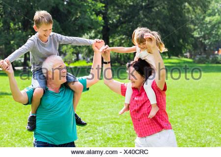 Heureux grands-parents petits-enfants donnant Piggyback Ride Banque D'Images