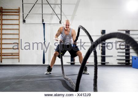 La formation de l'homme luttant avec des cordes dans la salle de sport Banque D'Images