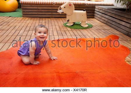 Baby Girl de ramper sur tapis orange, portrait Banque D'Images