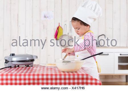 Petite fille de préparer des gaufres, portant chapeau de chef Banque D'Images
