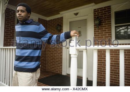 Portrait d'un jeune homme debout sur le porche avant de chambre Banque D'Images