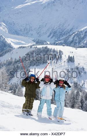 Groupe d'enfants debout dans la neige avec des skis Banque D'Images