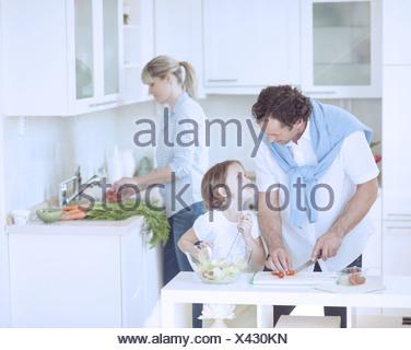 Père et fille à l'un l'autre tout en préparant des repas sains dans la cuisine Banque D'Images