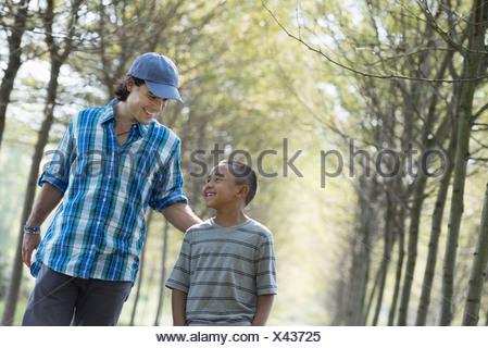 Un homme et un jeune garçon marchant dans une allée d'arbres. Banque D'Images