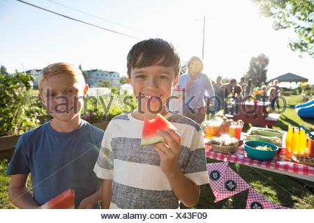 Portrait of smiling boys eating watermelon sunny park partie Banque D'Images