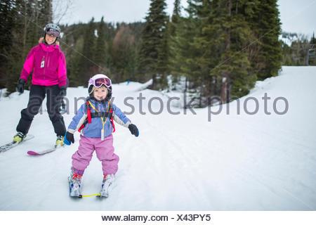 Little girl (2-3) l'apprentissage du ski avec la mère Banque D'Images