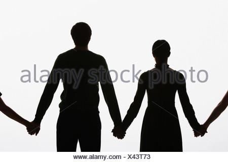 Quatre personnes debout main dans la main avec deux hors du champ Banque D'Images