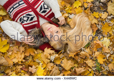 High angle view of young woman lying on autumn leaves in park Banque D'Images