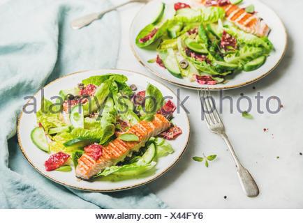 L'énergie saine stimuler salade de printemps avec du saumon grillé, d'orange sanguine, olives, concombre et le quinoa, selective focus, en arrière-plan. L'alimentation, Banque D'Images