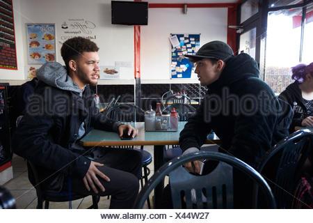 Deux étudiants hommes manger repas au Café Banque D'Images