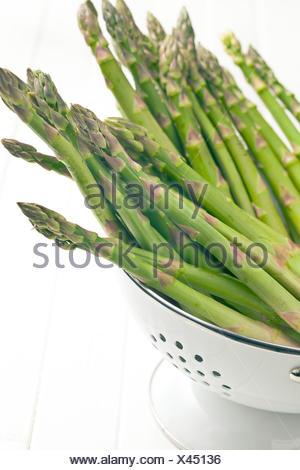 Les asperges vertes dans une passoire sur fond blanc Banque D'Images