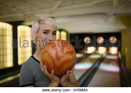 Confiant Portrait young woman holding bowling ball Banque D'Images