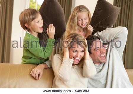Happy Family having fun avec des oreillers sur canapé Banque D'Images