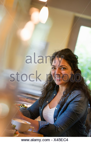 Une femme assise dans un café Banque D'Images