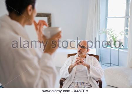 Portrait of a young woman holding une tasse de café avec un homme mûr assis sur une chaise à l'arrière-plan Banque D'Images