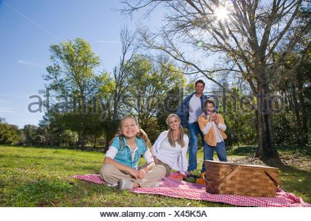 Jeune famille heureuse en parc avec panier pique-nique Banque D'Images