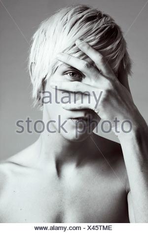 Un jeune homme aux cheveux blonds cachant son visage avec sa main Banque D'Images