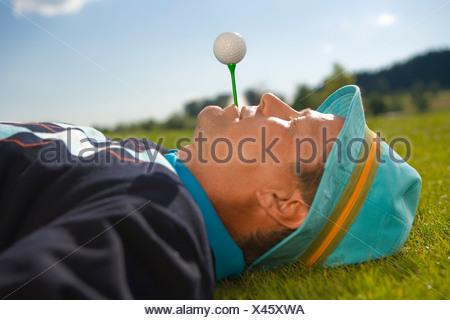 Close-up of a Mid adult man holding a té dans sa bouche avec une balle de golf en équilibre sur elle Banque D'Images