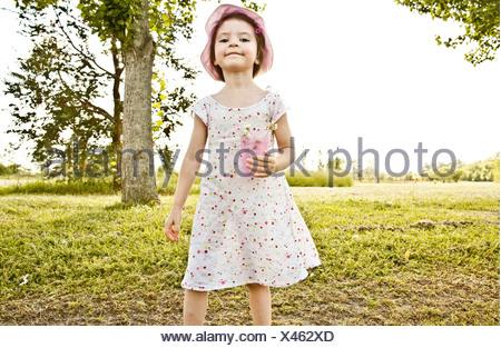 Petite fille au parc, holding cup de fleurs Banque D'Images