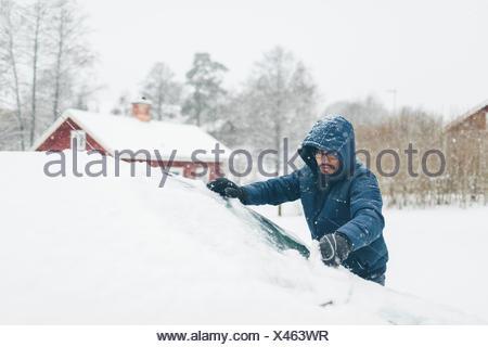 L'homme de sa voiture de la neige Banque D'Images