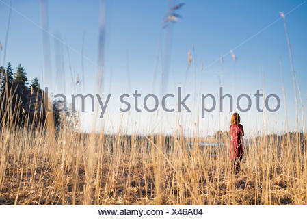 La Finlande, jeune femme World, standing in field in sunlight Banque D'Images