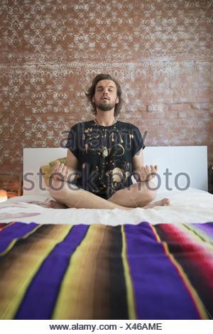 Jeune homme méditant sur son lit Banque D'Images