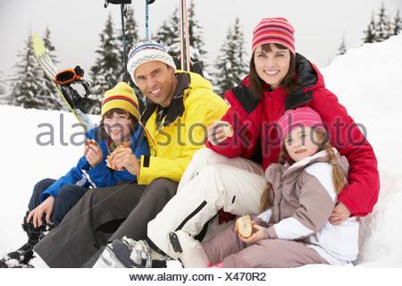 Family Eating Sandwich sur vacances de neige en montagne Banque D'Images