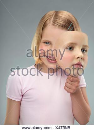 Portrait d'une jeune fille tenant un masque, studio shot Banque D'Images