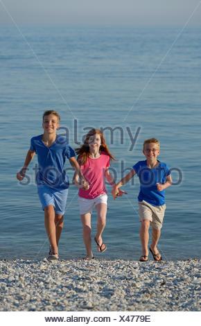 L'Italie, trois enfants souriants en marche main dans la main sur la plage de galets en face de la mer Banque D'Images