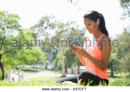 Young woman listening to mp3 player in park