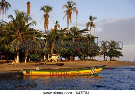 Petit bateau peint en couleurs reggae sur une plage tropicale avec palmiers, Puerto Viejo de Talamanca sur la côte des Caraïbes Banque D'Images