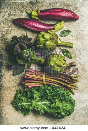 Télévision à jeter des légumes frais vert et violet sur fond de béton divers, vue d'en haut. produits locaux de saison pour la cuisine saine. eggplans, fèves, Banque D'Images