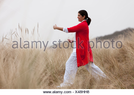 Woman practicing yoga on beach Banque D'Images