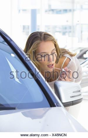 Woman applying lip gloss dans rétroviseur de voiture à car dealership showroom Banque D'Images