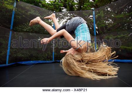 Girl jumping on trampoline en plein air Banque D'Images