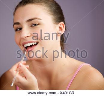 Une adolescente d'appliquer Lip Gloss Banque D'Images