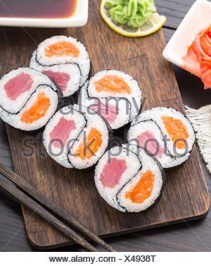 Yin Yang futomaki avec le thon et le saumon sur une planche en bois Banque D'Images