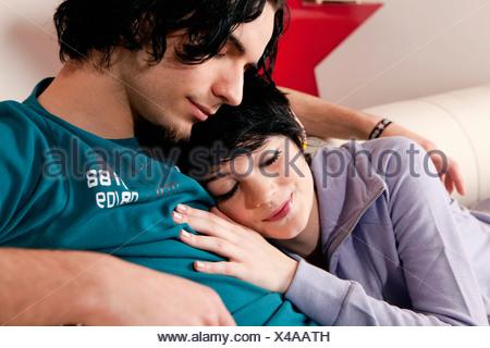 Portrait of young couple in tendre étreinte sur canapé Banque D'Images