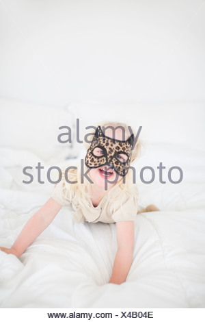 Masque de chat girl lying on bed Banque D'Images