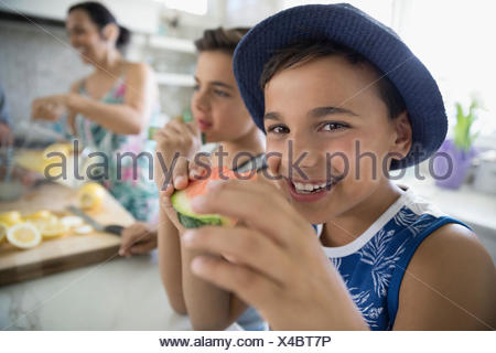 Portrait of smiling boy eating watermelon in kitchen Banque D'Images
