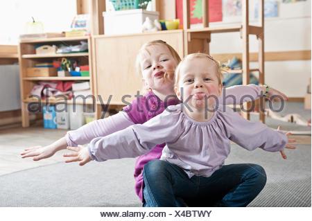 Portrait de deux petites sœurs de la maternelle collage hors de langues Banque D'Images